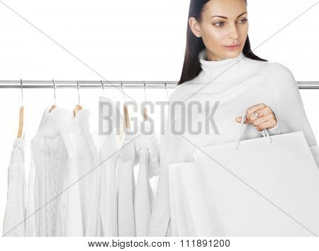 Young female with white shopping bags. Selection of winter clothes on background. Space for text. Sale season concept.