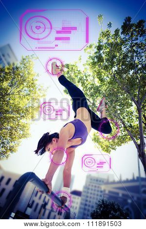 Athletic woman performing handstand on bar against fitness interface