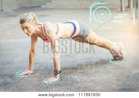 A pretty woman doing push-ups on the floor against fitness interface