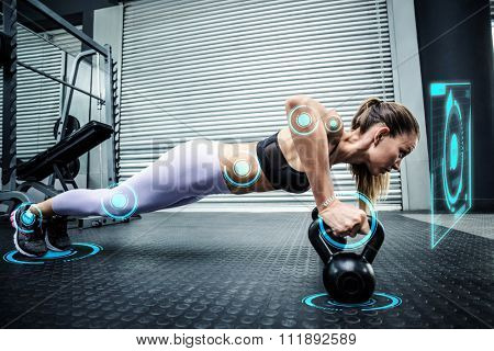 Muscular woman doing pushups with kettlebells against fitness interface