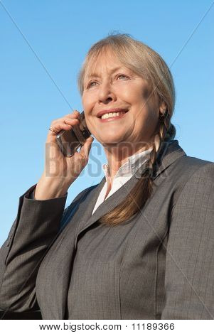 Happy mature businesswoman using cellphone