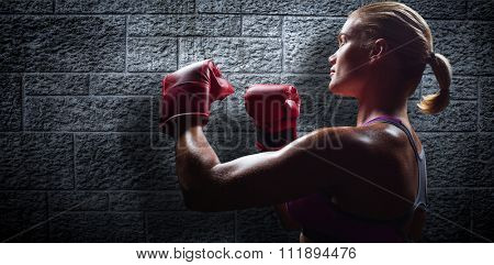 Side view of female boxer with fighting stance against grey brick wall