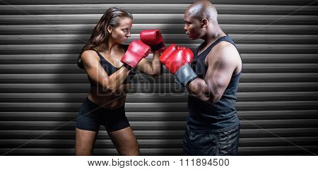 Male and female boxer with fighting stance against grey shutters