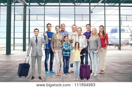 generation, travel, tourism and people concept - group of smiling people with luggage over airport terminal background