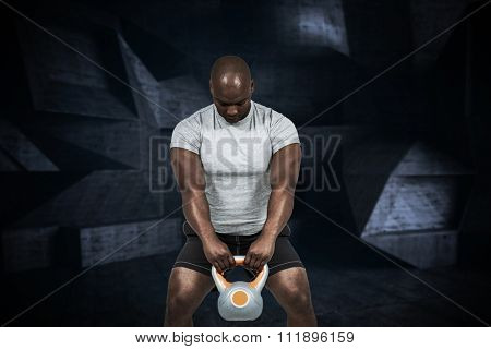 Fit man exercising with kettlebell against black angular design