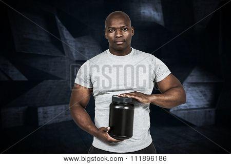 Fit man with protein powder against black angular design