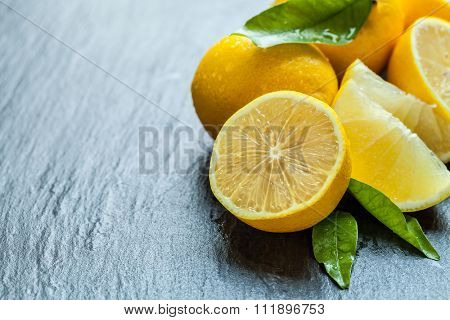 Fresh lemon fruit placed on black stone, low depth of focus