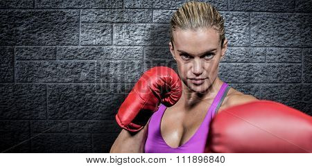 Portrait of female boxer with fighting stance against grey brick wall
