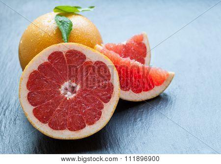 Fresh grapefruit placed on black stone. Low depth of focus