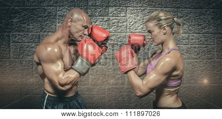 Side view of boxers with fighting stance against grey brick wall