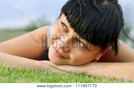 closeup of beautiful dreamy woman face that lies on grass