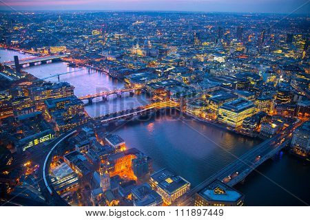City of London panorama at sunset. River Thames, bridges and lit up streets aerial view