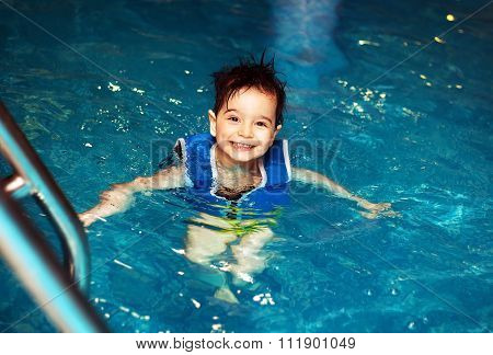 Young boy with inflatable swimming vest in the pool, has a happy smile. Eye contact