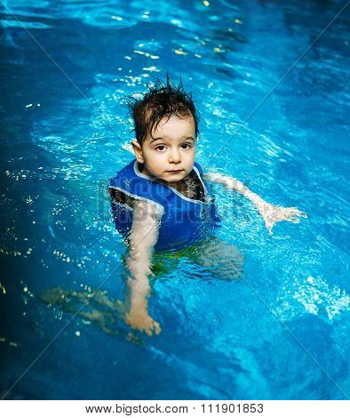 Young boy with inflatable swimming vest in the pool, has a happy smile.  Eye contact.