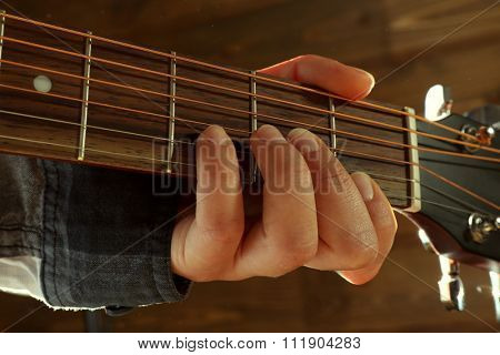 Guitars neck in guitarist hands on wooden background, close up