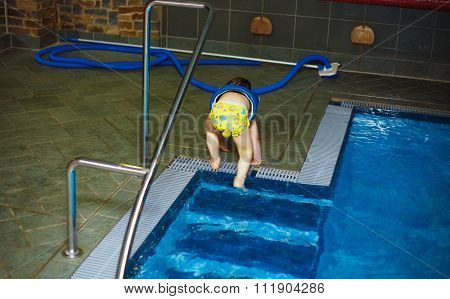 Young boy with inflatable swimming vest in the pool, has a happy smile.