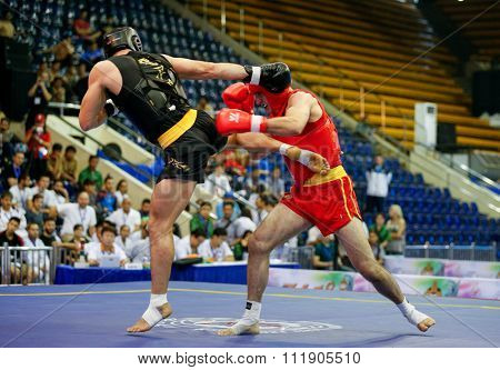JAKARTA, INDONESIA - NOVEMBER 18, 2015: Nicholas Evagorou of Great Britain (red) fights Amir Fazli of Iran (black) in the men's 85kg Sanda event at the 13th World Wushu Championship 2015.