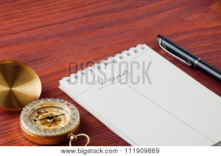Notepad With Handwritten Word Trends, Pen And Compass Nearby On Wooden Board Shallow Depth Of Field