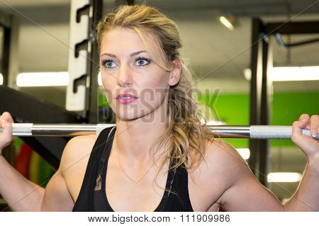 Sporty Blond Woman Exercising With Barbell In Gym