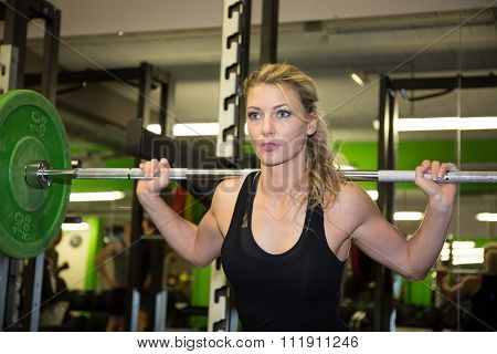 Strong Woman Lifting Barbell As A Part Of Exercise Routine.