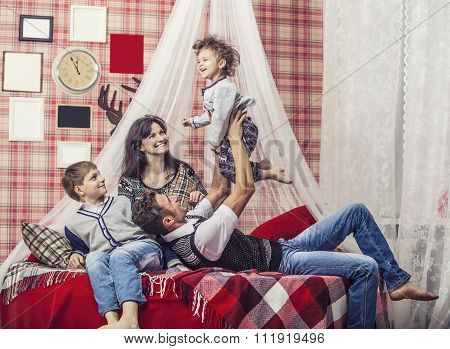 Family Mum Dad And Kids Together At Home In The Cosy Atmosphere Of The Bedrooms