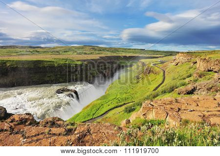 Grand Gullfoss in Iceland. Summer sunny day. Roaring water lit by the morning sun. The river banks are overgrown with green moss northern