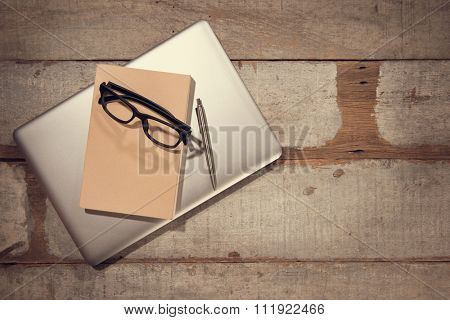 Work desk with laptop computer, diary book, pen and eyeglasses. Top view rustic wooden table background with copy space in vintage toned.