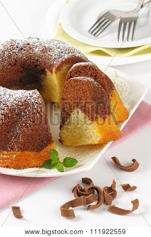 close up of sliced marble bundt cake on white plate and pink napkin