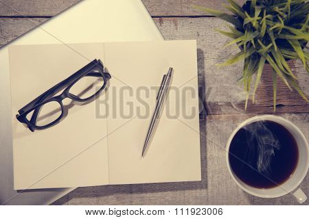 Work desk with laptop computer, diary book, pen, eyeglasses and hot coffee cup. Top view rustic wooden table background with copy space in vintage toned.