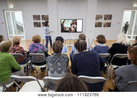 RUSSIA, MOSCOW - 18 MAY, 2015: Many visitors is sitting near display with restored after a fire picture in gallery at the center of Grabar.