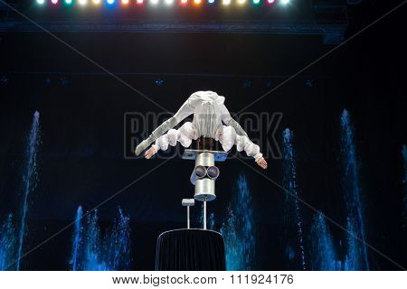 RUSSIA, MOSCOW - 18 DEC, 2014: Performer is doing tricks and standing on the head on a cylinders at Aquamarine circus.