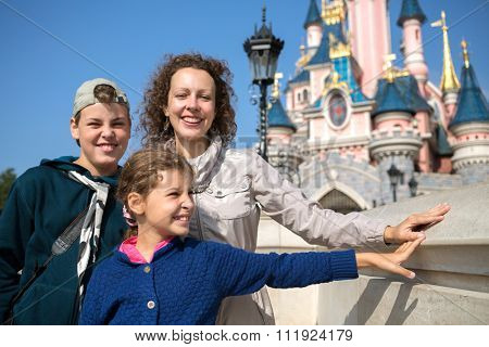 FRANCE, PARIS - 10 SEP, 2014: Young woman with her children (with model releases) are standing near Disneyland castle.