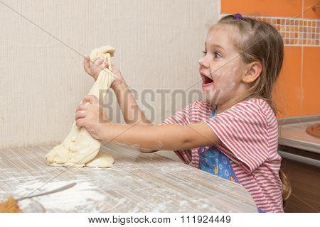 Cheerful Girl Tears Off A Piece Of Dough