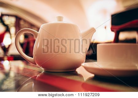 White teapot and teacup at restaurant.