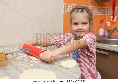 The Girl Rolls The Dough With A Rolling Pin Pancake For Pies And Looks In The Picture