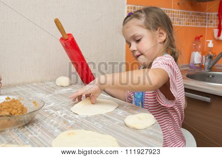 The Girl Rolls The Dough With A Rolling Pin For Pies