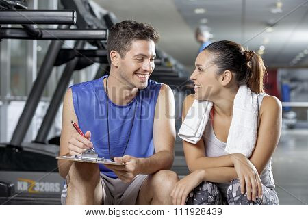 Male Trainer Sitting In Gym With Client