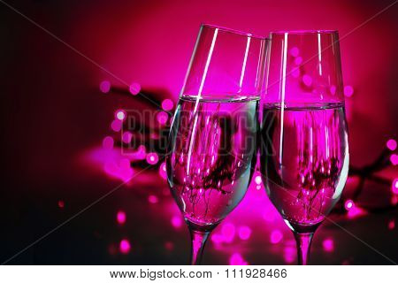 Two Champagne Flutes Clink Glasses On New Year's Party, Purple Background With Blurred Lights