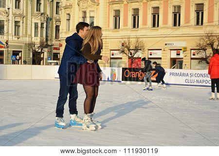 Young Couple Skating On Ice Skating Rink
