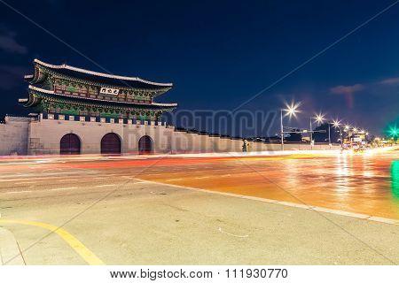 Night Shot Of Gwanghwamun Gate Of Gyeongbokgung Palace In Seoul, South Korea With Taillights And Hea
