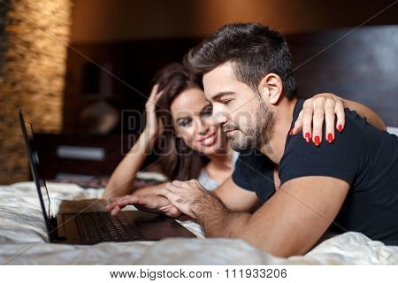 Young Couple Online Shopping On Bed By Laptop