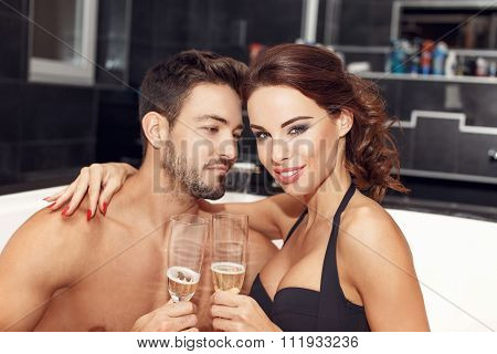 Happy Young Couple Drink Champagne In Jacuzzi