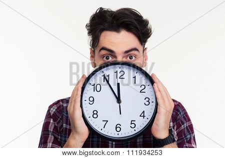 Portrait of a young man covering her face with wall clock isolated on a white background