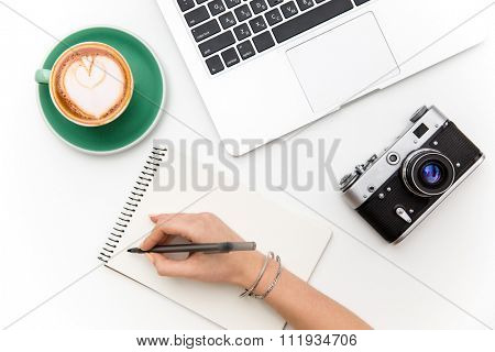 Top view of laptop, old camera, cup of coffee and woman hand writing in notebook over white background
