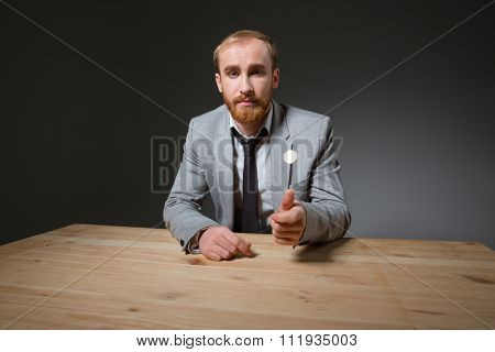 Handsome businessman sitting at the table and throwing coin over dark background