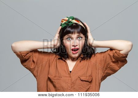 Shocked dazed young woman with opened mouth holding head by hands isolated over grey background
