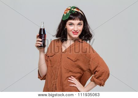 Attractive confident young woman posing with  bottle of sweet carbonated beverage isolated over grey background