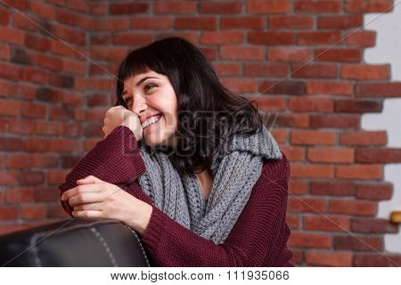 Charming shy young woman in knitted gray scarf sitting on leather sofa and laughing over brick wall background
