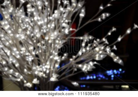 Blurred Christmas Background: White Bush With Glowing Lights.