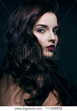 beauty young brunette woman with curly flying hair, femme fatal on black background, low key
